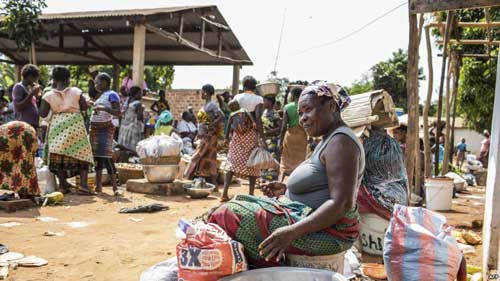 FILE - A vendor waits for customers to exchange her goods for other goods at the barter market in Togoville, Nov. 24, 2018. Every Saturday on the northern shore of Lake Togo, some 65 kilometers (40 miles) east of the capital, Lome, Togoville runs a lively barter market.