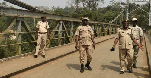 Puis Utomi Ekpei, AFP | Immigration officers walk on a suspension bridge built in 1948 that connects Nigeria with Cameroon at Mfum border station in Cross Rivers State, southeast Nigeria on February 1, 2018.