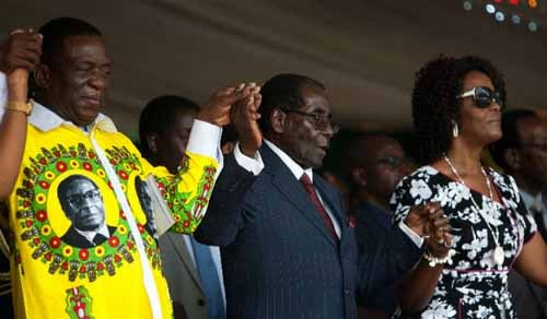 Back when they were friends: Emmerson Mnangagwa (left) and the Mugabe couple hold hands during celebrations to mark the president's birthday on February 27, 2016. © Jekesai Njikizana, AFP