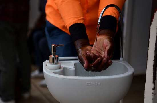 A man washes his hands at a public hand washing station before boarding a bus as a cautionary measure against the coronavirus at the Nyabugogo Bus Park in Kigali, Rwanda. March 11, 2020. REUTERS/Maggie Andresen
