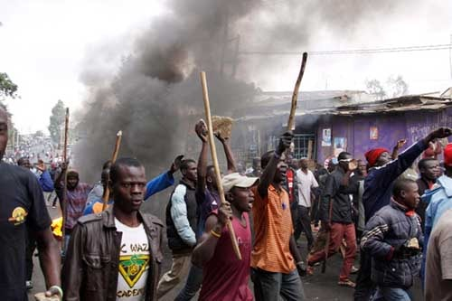 Supporters of opposition leader Raila Odinga march with sticks in the Kibera slum of Nairobi on Saturday. Violent demonstrations have erupted in some areas after President Uhuru Kenyatta was declared victorious in the presidential election. Photo - AP