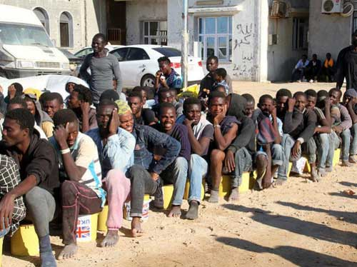 African migrants being displayed under the 'For Sale' sign in Libya. Getty image