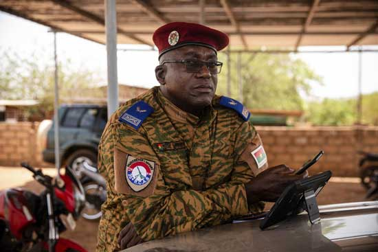 "Salomon Tibiri, a pastor and military chaplain, checks his phone at the 10th RCAS barracks in Kaya, Burkina Faso, Saturday, April 10, 2021. Tibiri has been offering soldiers spiritual succor for more than 15 years. But he's never fielded as many calls from anxious soldiers as in recent years, when the army found itself under attack by Islamic extremist fighters. ""Now (the soldiers) are busier, and when you approach them you feel their stress — much more stress,"" he says. (AP Photo/Sophie Garcia)"