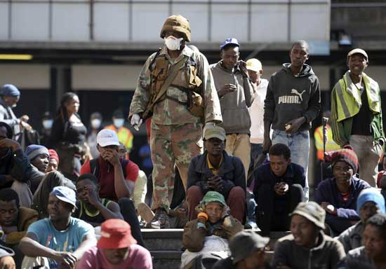 A soldier watches homeless people who were rounded up in downtown Johannesburg Friday, March 27, 2020, after South Africa went into a nationwide lockdown for 21 days in an effort to mitigate the spread to the coronavirus. The new coronavirus causes mild or moderate symptoms for most people, but for some, especially older adults and people with existing health problems, it can cause more severe illness or death. (AP Photo)