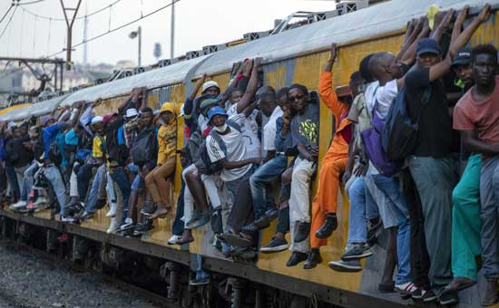Train commuters hold on to the side of an overcrowded passenger train in Soweto, South Africa, Monday, March 16, 2020. South Africa will revoke nearly 10,000 visas issued this year to people from China and Iran, and visas will now be required for other high-risk countries that had been visa-free, including Italy and the United States. For most people, the new coronavirus causes only mild or moderate symptoms. For some it can cause more severe illness, especially in older adults and people with existing health problems.(AP Photo/Themba Hadebe)