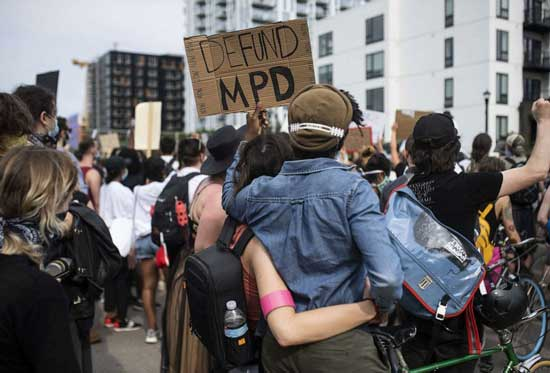 In this June 6, 2020, file photo, demonstrators calling to defund the Minneapolis Police Department march on University Avenue in Minneapolis.