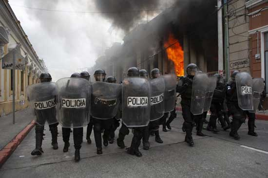 Riot police form a cordon as flames shoot out from the Congress building after protesters set a part of the building on fire, in Guatemala City, Saturday, Nov. 21, 2020. Hundreds of protesters were protesting in various parts of the country Saturday against Guatemalan President Alejandro Giammattei and members of Congress for the approval of the 2021 budget that reduced funds for education, health and the fight for human rights. (AP Photo/Oliver De Ros)
