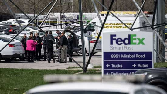 A group of crime scene investigators gather to speak in the parking lot of a FedEx SmartPost on April 16, 2021, in Indianapolis.