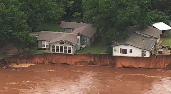 This image taken from video provided by KOCO-5 shows homes dangerously close to the Cimarron River, May 22, 2019, near Crescent, Oka.