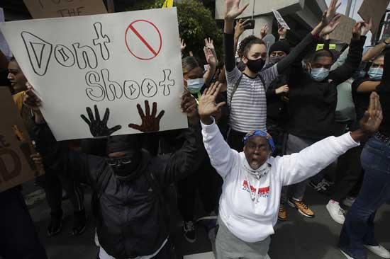 People yell while kneeling in San Francisco, Sunday, May 31, 2020, at protests over the Memorial Day death of George Floyd. Floyd was a black man who was killed in police custody in Minneapolis on May 25. (AP Photo/Jeff Chiu)