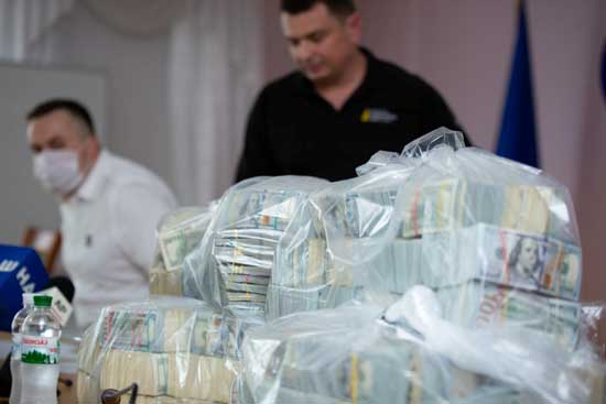 Plastic bags filled with U.S. Dollar banknotes seized by the National Anti-Corruption Bureau of Ukraine are seen on a table during a news briefing at the anti-corruption prosecutor's office in Kiev, Ukraine June 13, 2020. Press Service of the National Anti-Corruption Bureau of Ukraine/Handout via REUTERS