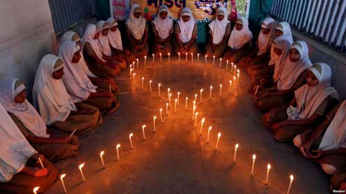 FILE - School girls light candles in the shape of a ribbon during a HIV/AIDS awareness campaign ahead of World Aids Day, in Ahmedabad, India, Nov. 30, 2016.