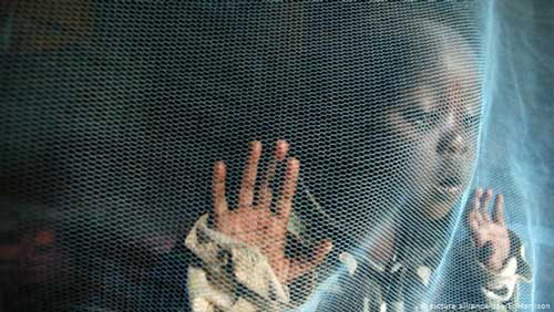 A child stands behind a mosquito net (picture alliance/dpa/E. Morrison)