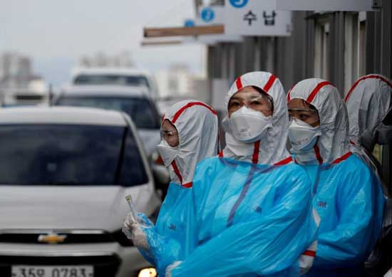 FILE PHOTO: Medical staff in protective gear work at a 'drive-thru' testing center for the novel coronavirus disease of COVID-19 in Yeungnam University Medical Center in Daegu, South Korea, March 3, 2020. REUTERS/Kim Kyung-Hoon