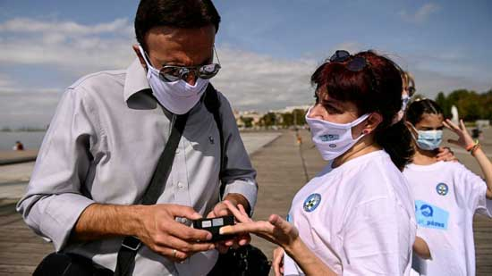 Greek doctors march and measure to promote use of face masks. AP photo