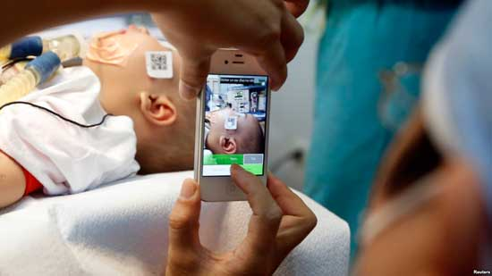 FILE - A doctor uses a smartphone to take a photo of a child with facial deformity before surgery at the Vietnam Cuba hospital in Hanoi, Vietnam.