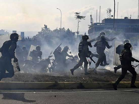 Members of the Bolivarian National Guard loyal to Venezuelan President Nicolas Maduro run under a cloud of tear gas after being repelled with rifle fire by guards supporting Venezuelan opposition leader Juan Guaido in Caracas, April 30, 2019.
