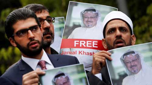 Human rights activists and friends of Saudi journalist Jamal Khashoggi hold his pictures during a protest. Image credit - CNBC