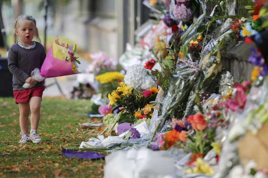 A girl walks to lay flowers on a wall at the Botanical Gardens in Christchurch, New Zealand, Sunday, March 17, 2019. New Zealand's stricken residents reached out to Muslims in their neighborhoods and around the country on Saturday, in a fierce determination to show kindness to a community in pain as a 28-year-old white supremacist stood silently before a judge, accused in mass shootings at two mosques that left dozens of people dead. (AP Photo/Vincent Thian)