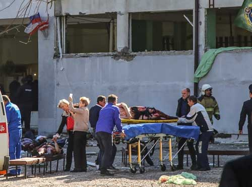 Rescuers carry an injured victim of a blast at a college in the city of Kerch. Image credit - News wires