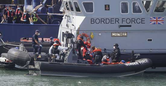 A Border Force vessel brings a group of people thought to be migrants into the port city of Dover, England, from small boats, Saturday Aug. 8, 2020.  AP photo