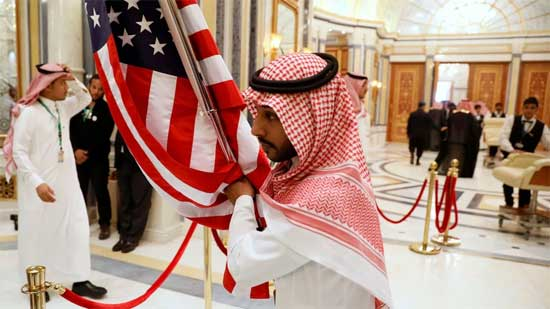 FILE PHOTO: A worker carries a U.S. flag into a meeting room ahead of U.S. President Donald Trump's meeting with Gulf Cooperation Council leaders in Riyadh.