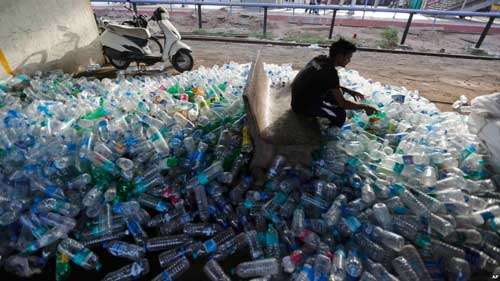 An Indian worker sorts used plastic bottles before sending them to be recycled, at a railway station on World Environment Day in Ahmadabad, India, June 5, 2018. VOA photo
