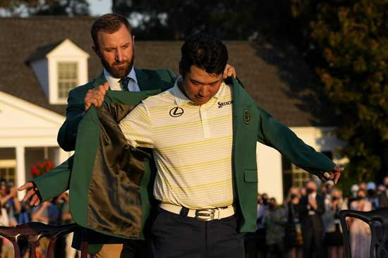 Hideki Matsuyama, of Japan, puts on the champion's green jacket with help from Dustin Johnson after winning the Masters golf tournament on Sunday, April 11, 2021, in Augusta, Ga. (AP Photo/David J. Phillip)