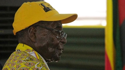 Zimbabwean President Robert Mugabe sweats as he leaves the podium after delivering his speech during the official opening of the Zanu pf 6th National Congress in Harare, Thursday, Dec. 4, 2014. Mugabe attacked his deputy President Joice Mujuru aledging she plotted to remove him from power.