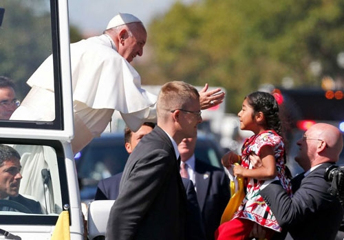 Pope Francis reaches from the popemobile for a child that is brought to him, during a parade in Washington, Wednesday, Sept. 23, 2015.