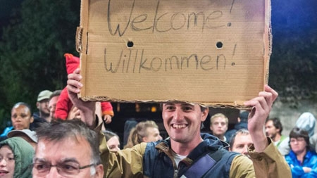 A man holds a cardboard with a 'Welcome' slogan during the arrival of refugees at the train station in Saalfeld, central Germany, Saturday, Sept. 5, 2015