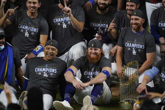 os Angeles Dodgers manager Dave Roberts and third baseman Justin Turner pose for a group picture after the Dodgers defeated the Tampa Bay Rays 3-1 in Game 6 to win the baseball World Series, Tuesday, Oct. 27, 2020, in Arlington, Texas. (AP Photo/Eric Gay)